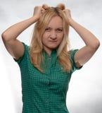 Gniewna młoda kobieta w przypadkowej zielonej koszula z rękami w włosach zdjęcie royalty free