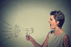 Gniewna młoda kobieta krzyczy z megafonem Zdjęcia Royalty Free