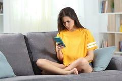 Gniewna nastoletnia czytelnicza online zawartość w telefonie obrazy stock