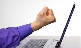 Gniewna pięść podnosząca przy laptopu ekranem Obrazy Stock