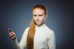 Gniewna rudzielec dziewczyna z telefonem komórkowym Odizolowywający na szarość zdjęcie royalty free