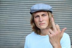 Gniewna samiec pokazuje grubiańskiego gest na szarym tle Obrazy Stock
