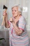 Gniewna stara kobieta z ax Zdjęcia Stock
