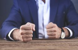Gniewne mężczyzna pięści na drewnianym stołowym tle obrazy royalty free