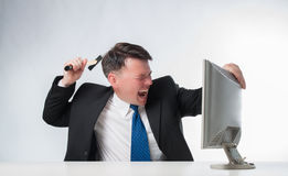 Gniewni mężczyzna trzyma młoteczkowego nadmiernego peceta monitoru Obraz Stock