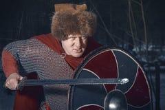 Gniewny średniowieczny wojownik z kordzikiem i osłoną fotografia stock