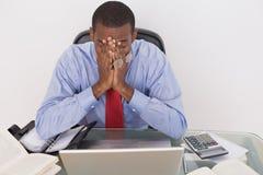Gniewny Afro biznesmen z rękami na twarzy przy biurkiem Fotografia Stock