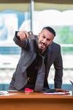 Gniewny agresywny biznesmen z pistoletem w biurze Zdjęcia Stock