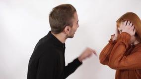 Gniewny agresywny mężczyzna wrzeszczy przy jego piękną dziewczyną z długim czerwonym włosy Kobieta zamknięta jej ucho i twarz, no zbiory wideo