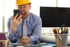 Gniewny architekta projektanta krzyk Dzwonić w ręce obrazy stock