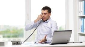 Gniewny biznesmen dzwoni na telefonie z laptopem zdjęcie wideo