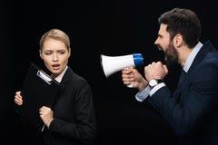Gniewny biznesmen krzyczy na koledze z głośnikiem Obraz Royalty Free