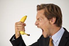 Gniewny biznesmen krzyczy przy bananem Zdjęcie Royalty Free