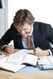 Gniewny biznesmen pracuje przy biurkiem Zdjęcie Royalty Free