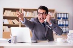 Gniewny biznesmen pracuje w biurze Obrazy Royalty Free