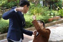 Gniewny biznesmen uderza jego rywala w parku Fotografia Royalty Free