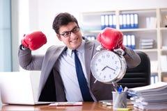 Gniewny biznesmen z bokserskimi rękawiczkami w czasu zarządzania pojęciu Zdjęcie Stock