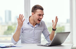 Gniewny biznesmen z laptopem i papierami w biurze Fotografia Stock