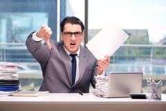 Gniewny biznesmen z zbyt dużo pracy w biurze zdjęcia stock