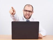Gniewny biznesmena obsiadanie przy jego krzyczeć i biurkiem Zdjęcie Stock