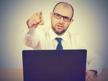 Gniewny biznesmena obsiadanie przy jego krzyczeć i biurkiem Fotografia Stock
