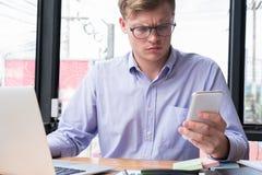Gniewny biznesmena use telefon komórkowy przy miejscem pracy mężczyzna texting mesa Zdjęcie Royalty Free