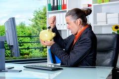 Gniewny biznesowy mężczyzna przy jego biurkiem z prosiątko bankiem Zdjęcie Stock