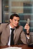 Gniewny biznesowy mężczyzna trzyma telefonicznego odbiorcę Obrazy Stock