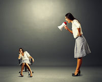 Gniewny bizneswoman krzyczy przy gnuśną kobietą obraz stock