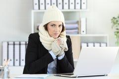Gniewny bizneswoman ma zimno przy biurem fotografia stock