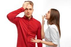Gniewny brodaty mężczyzna stawia jego rękę na jego czole, kobieta wrzaski z negatywnymi emocjami na koledze obraz royalty free