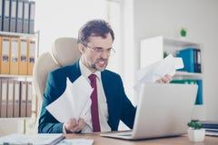 Gniewny businessmsn pośrednik handlu nieruchomościami jest krzyczący przy jego laptopem przy jego wor obrazy royalty free