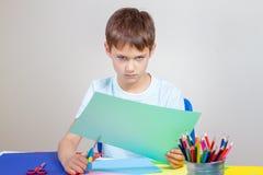 Gniewny dziecka rozcięcie barwił papier z nożycami przy stołem zdjęcia royalty free