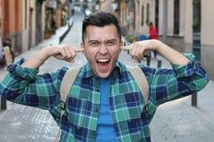 Gniewny główny nakrycie jego ucho outdoors zdjęcia stock