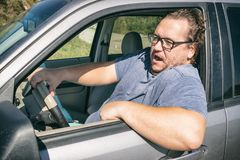 Gniewny gruby mężczyzna w samochodzie Droga i stres zdjęcie royalty free
