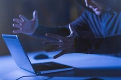 Gniewny hacker krzyczy w ciemnym pokoju z laptopem Obraz Royalty Free