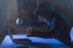 Gniewny hacker krzyczy w ciemnym pokoju z laptopem Zdjęcia Stock