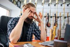 Gniewny i zmęczony młody modniś siedzi przy stołem w pokoju Trzyma ręki blisko do głowy Facet migrenę Wiele gitary elektryczne zdjęcia stock
