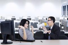 Gniewny kierownik z sekretarką w miejscu pracy obraz royalty free
