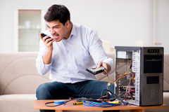 Gniewny klient próbuje naprawiać komputer z telefonu poparciem Zdjęcie Stock