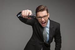 Gniewny kryminalny biznesmen z pistoletem na popielatym tle obraz royalty free