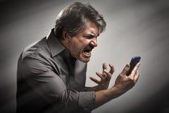 Gniewny krzyczący mężczyzna z telefonem komórkowym zdjęcia royalty free
