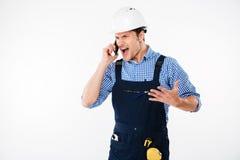 Gniewny krzyczący młody budowniczy opowiada na telefonie obrazy royalty free