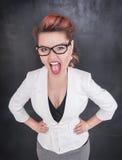 Gniewny krzyczący nauczyciel na blackboard tle fotografia stock