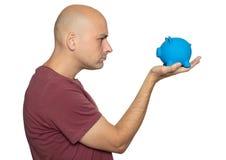 Gniewny mężczyzna patrzeje prosiątko banka zdjęcia royalty free