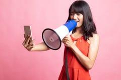 Gniewny młody Azjatycki kobieta krzyk z megafonem telefon komórkowy zdjęcia stock