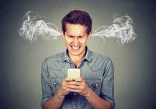 Gniewny mężczyzna czyta wiadomość tekstową na smartphone dmuchania kontrpary przybyciu z ucho zdjęcie stock