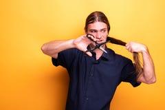 Gniewny mężczyzna decydował ciąć jego długie włosy z nożycami zdjęcia stock