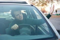 Gniewny mężczyzna kierowca sikał daleko kierowcami przed on i gestu Obrazy Royalty Free