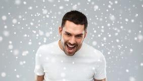 Gniewny mężczyzna krzyczy nad śnieżnym tłem obrazy stock